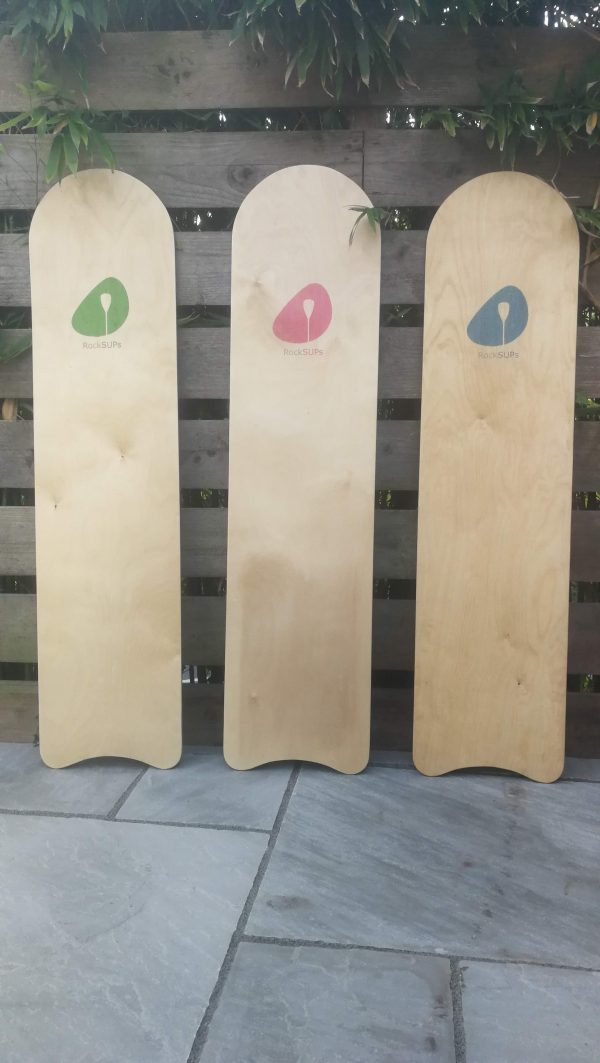 Photo of 3 belly boards displaying the logo colours